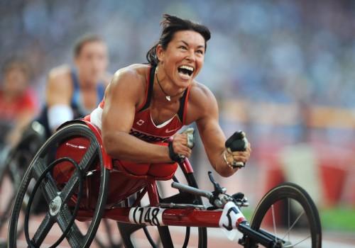 На фото: Шанталь Петиклерк празднует победу в соревнованиях на ручных велосипедах на Паралимпийских играх в Пекине.
