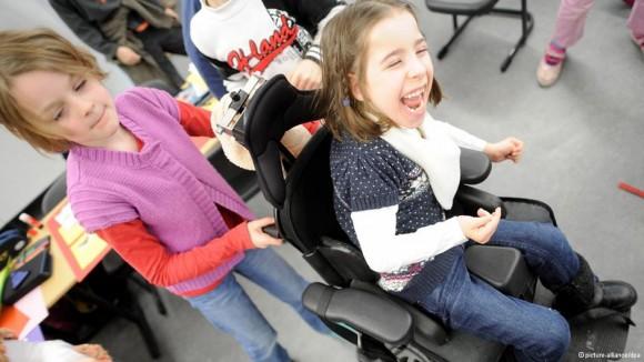 Одна ученица катит другую ученицу в инвалидном кресле В школе города Нойс учатся дети с разными физическими возможностями