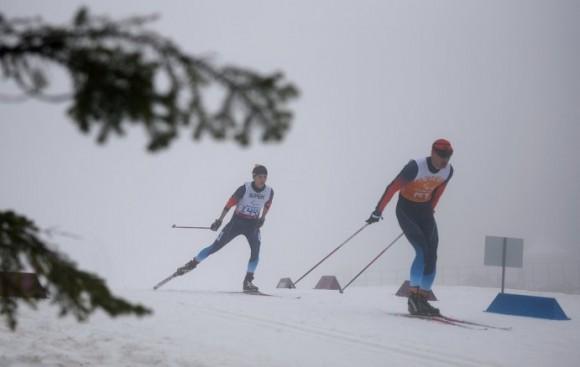 Михалина Лысова (Россия) и ведущий Алексей Иванов на трассе гонки на средней дистанции в классе B 1-3 (слабовидящие) среди женщин в соревнованиях по биатлону на XI Паралимпийских зимних играх в Сочи.