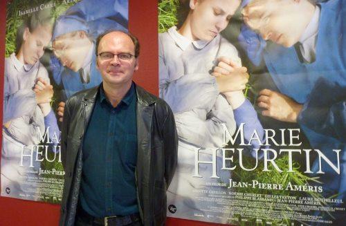 Жанн-Пьер Амери на фоне афиш своего нового фильма
