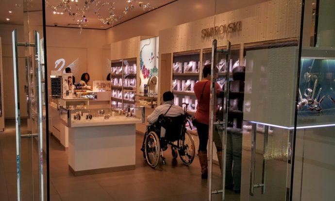 Инвалид в коляске выбирает подходящие ювелирные изделия в дорогом бутике